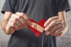 Broken hearted man. Valentines day concept. Man holding broken heart in his hands
